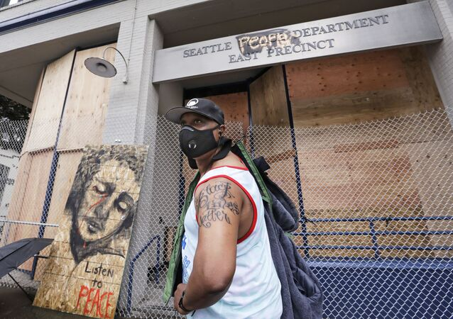 Rodney Maine displays his new Black Lives Matter tattoo after asking a passerby to take his photo in front of a plywood-covered and fenced-off Seattle police precinct Tuesday, June 9, 2020, in Seattle.