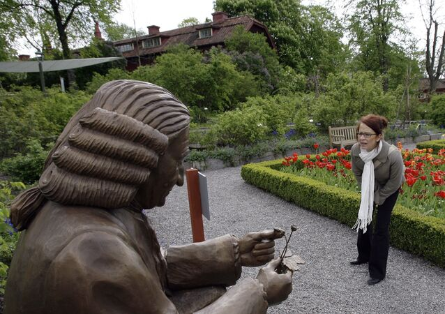 A woman looks at a statue of botanist Carl Linnaeus along the Linnaeus botanic track 18 May 2007 arranged for the 300 anniversary of Linnaeus' birth, in the Swedish national heritage park Skansen in Stockholm