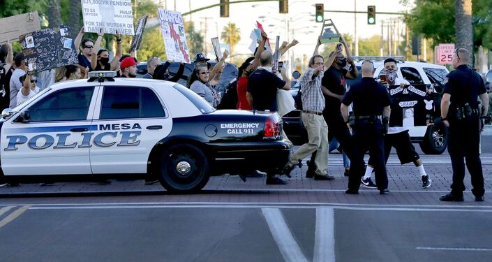 Protesters demanding police reform walk past Mesa police officers blocking a street, Tuesday, June 9, 2020, in Mesa, Ariz. The protest is a result of the death of George Floyd, a black man who died after being restrained by Minneapolis police officers on May 25