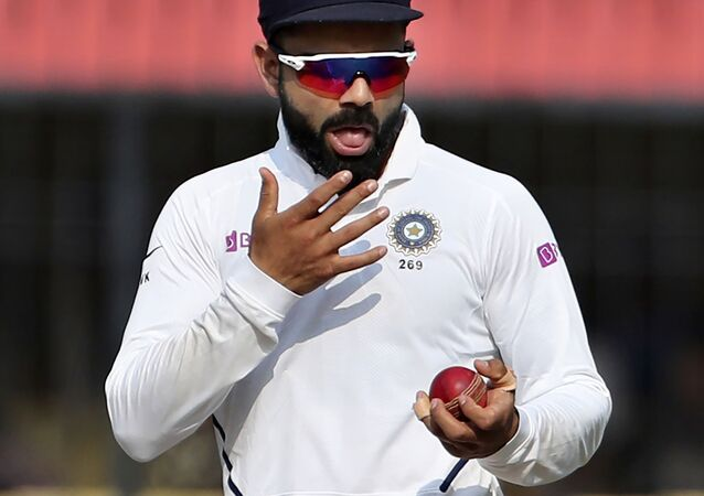 India's captain Virat Kohli shines the ball with saliva during a Test match against Bangladesh in Indore in November 2019.