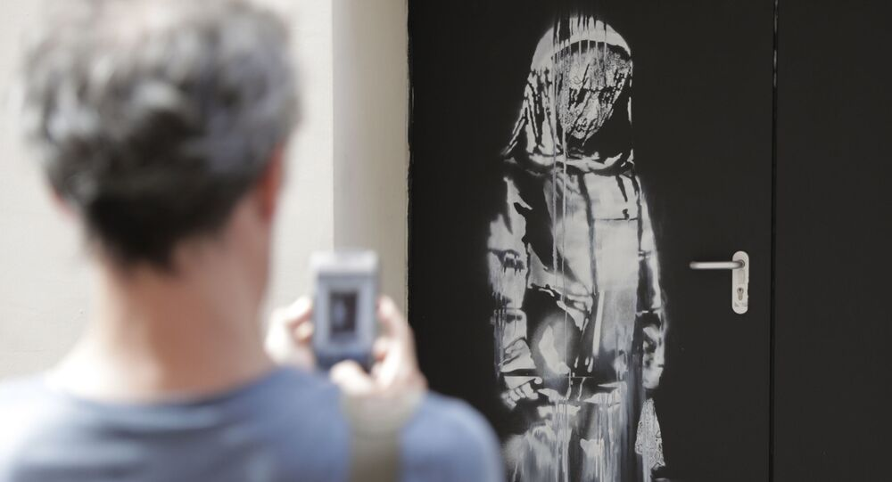 (FILES) In this file photo taken on June 25, 2018 a man takes a photograph of an artwork by street artist Banksy in Paris on a side street to the Bataclan concert hall where a terrorist attack killed 90 people on Novembre 13, 2015