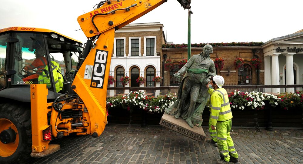 A statue of Robert Milligan is pictured being removed by workers from outside the Museum of London Docklands near Canary Wharf, following the death of George Floyd who died in police custody in Minneapolis, London, Britain