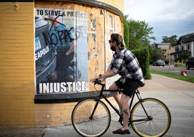 A cyclist passes a poster showing former Minneapolis police officer Derek Chauvin kneeling on George Floyd