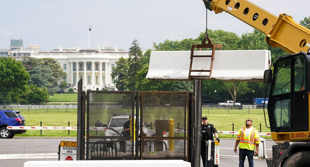 A pedestrian ducks under a concrete barrier while a crane removes barriers from around the White House as workers begin to take down fences that were installed during the recent demonstrations against racial inequality in the aftermath of the death in Minneapolis police custody of George Floyd, on the streets near the White House in Washington, U.S., June 10, 2020