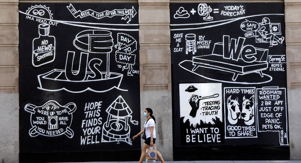 A woman wearing a protective face mask walks past graffiti on boarded up and closed storefronts in the Soho neighborhood of Manhattan during the outbreak of the coronavirus disease (COVID-19) in New York City, New York, U.S., May 26, 2020.