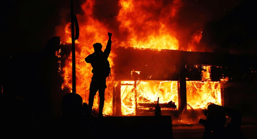 A protester gestures as buildings burn during continued demonstrations against the death in Minneapolis police custody of African-American man George Floyd, in Minneapolis, Minnesota, U.S., May 30, 2020