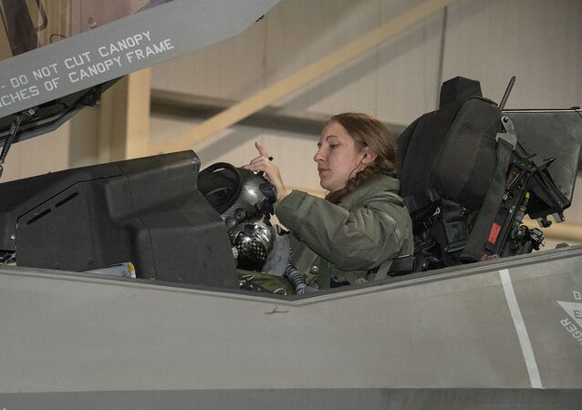 U.S. Air Force Capt. Emily Thompson, 421st Expeditionary Fighter Squadron pilot, dons her helmet prior to a mission on the Al Dhafra Air Base, United Arab Emirates, flightline June 5, 2020. Thompson is the first female to fly an F-35A Lightning II into combat. She is currently deployed from Hill Air Force Base, Utah