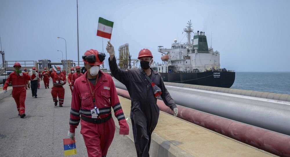 A worker of the Venezuelan state oil company PDVSA waves an Iranian flag as the Iranian-flagged oil tanker Fortune docks at the El Palito refinery in Puerto Cabello, in the northern state of Carabobo, Venezuela, on May 25, 2020