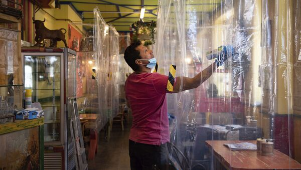 Cafe owner Francini Osorio sprays air sanitiser where he has installed an air purifier and 35 clear shower curtains - Sputnik International