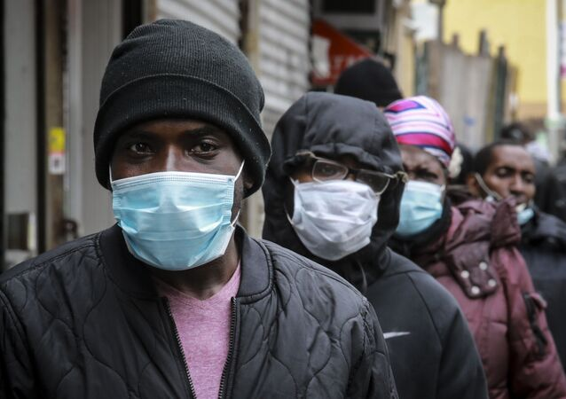 People wait for a distribution of masks and food from the Rev. Al Sharpton in the Harlem neighborhood of New York, after a new state mandate was issued requiring residents to wear face coverings in public due to COVID-19, Saturday, April 18, 2020