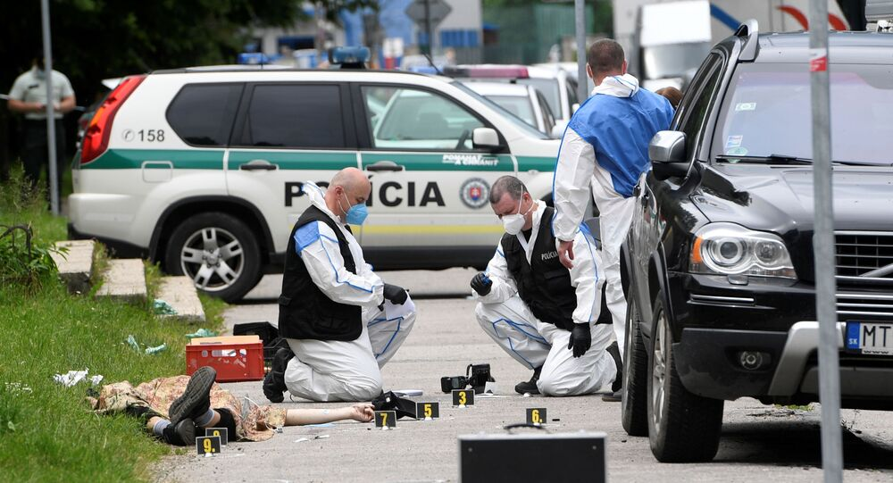 Forensic police officers wearing face masks work next to the body of an attacker as they inspect the scene of an assault on staff at a school in Vrutky, Slovakia, June 11, 2020