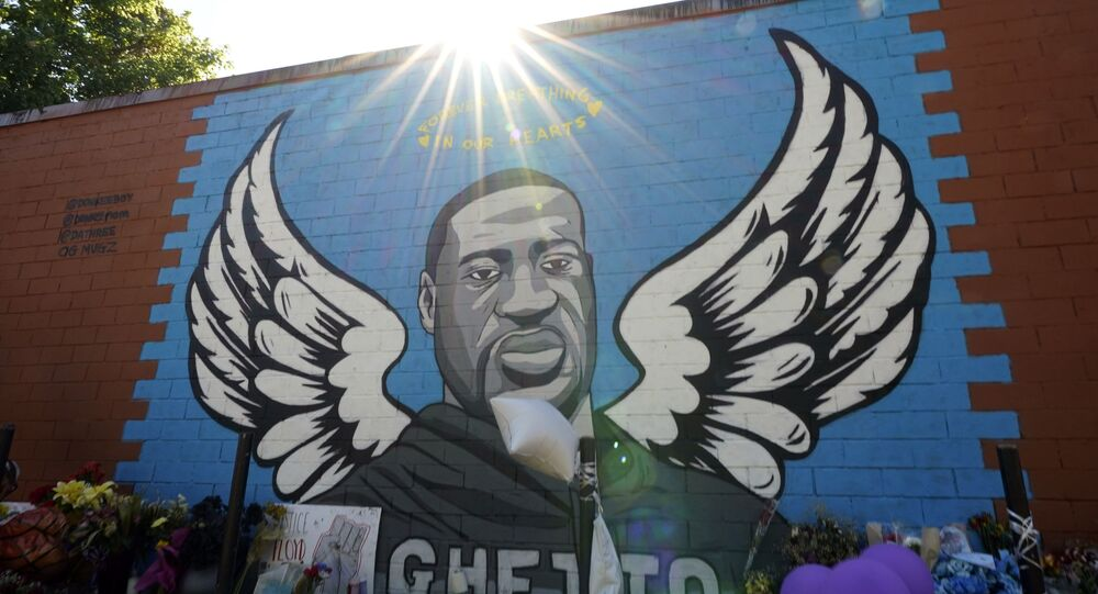 In this 7 June 2020 photo, the sun shines above a mural honouring George Floyd in Houston's Third Ward.