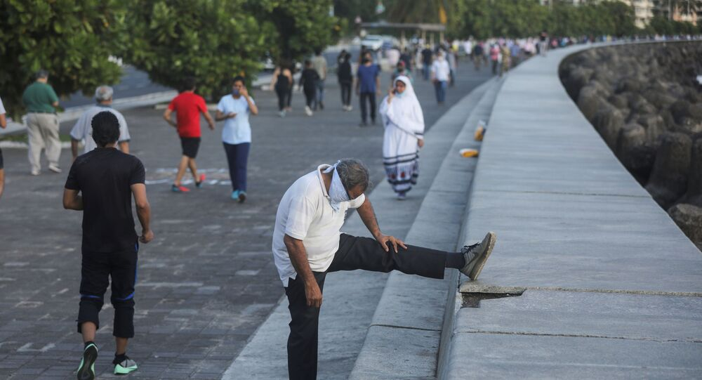 A man stretches his leg as people walk along the promenade at Marine Drive after some restrictions were lifted during a nationwide lockdown to slow the spread of the coronavirus disease (COVID-19), in Mumbai, India, June 8, 2020