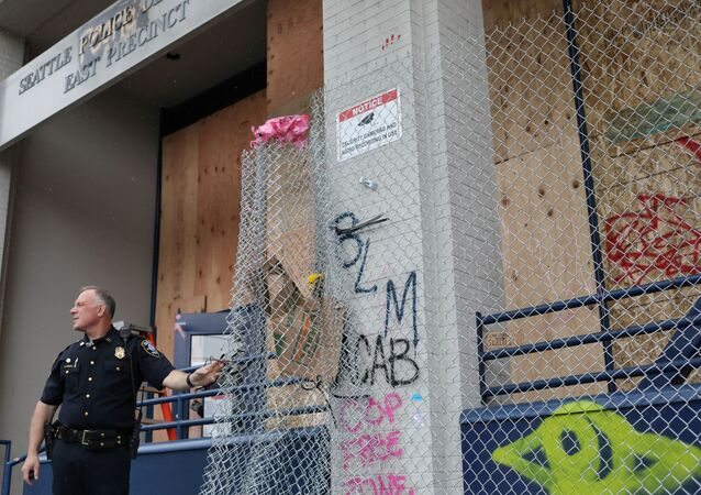 A police officer stands as he removes a wire barricade at the entrance of Seattle Police Department East Precinct in Seattle, Washington, U.S. June 11, 2020.