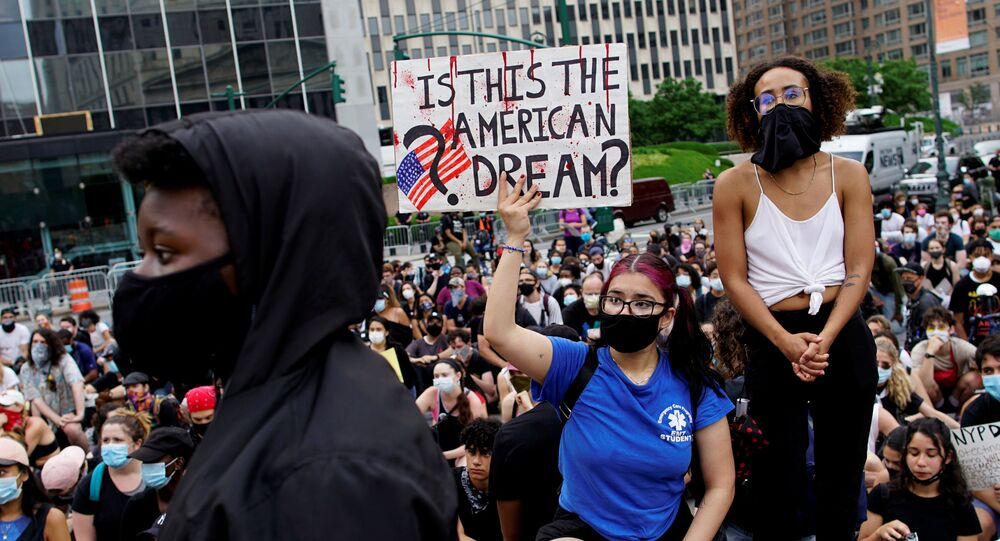 A protester holds a sign during a protest against police brutality and racial inequality in the aftermath of the death in Minneapolis police custody of George Floyd, in New York, U.S., June 11, 2020