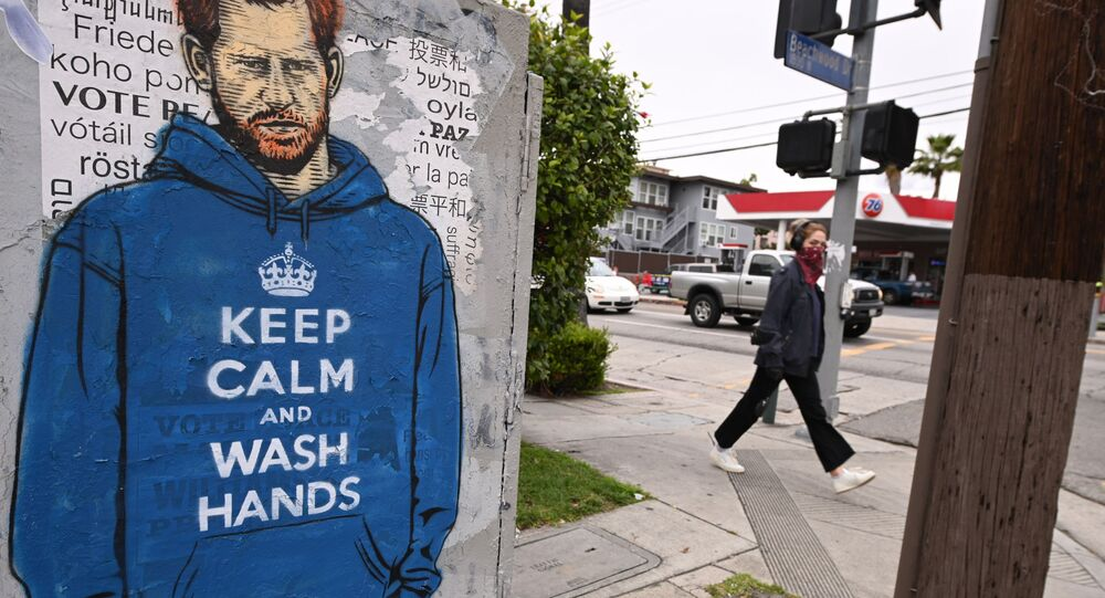 People walk past graffiti of Prince Harry wearing a hoodie reading Keep Calm and Wash Your Hands, on 7 April 2020, during the coronavirus pandemic in Los Angeles, California.
