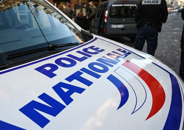 In this file photo taken on 3 December 2019, a French police officer stands next to a French Police Nationale car in Lille, northern France.