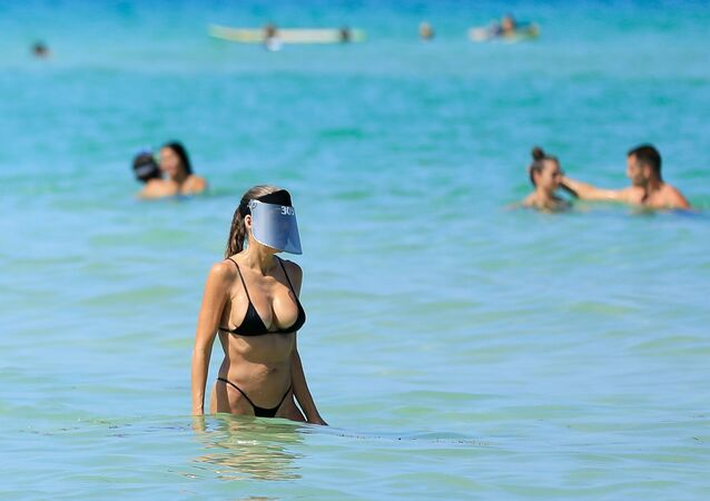 A woman wears a face shield as she wades in the ocean off South Beach on June 10, 2020 in Miami Beach, Florida.