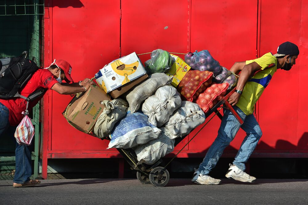 Two men carry a cart loaded with fresh goods at a street in Tegucigalpa, Honduras, on June 8, 2020, after the government announced the resumption of economic activity, amid the COVID-19 pandemic.