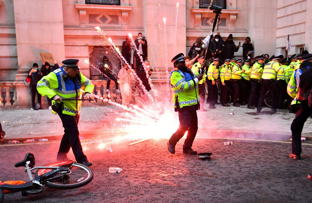 A firework explodes as police officers clash with demonstrators in Whitehall during a Black Lives Matter protest in London, following the death of George Floyd who died in police custody in Minneapolis, London, Britain, June 7, 2020.