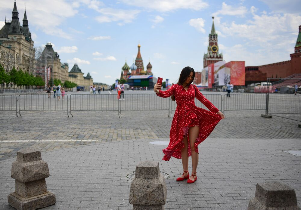A woman poses for a selfie at Red Square on a sunny day amid the coronavirus outbreak, in Moscow, Russia.
