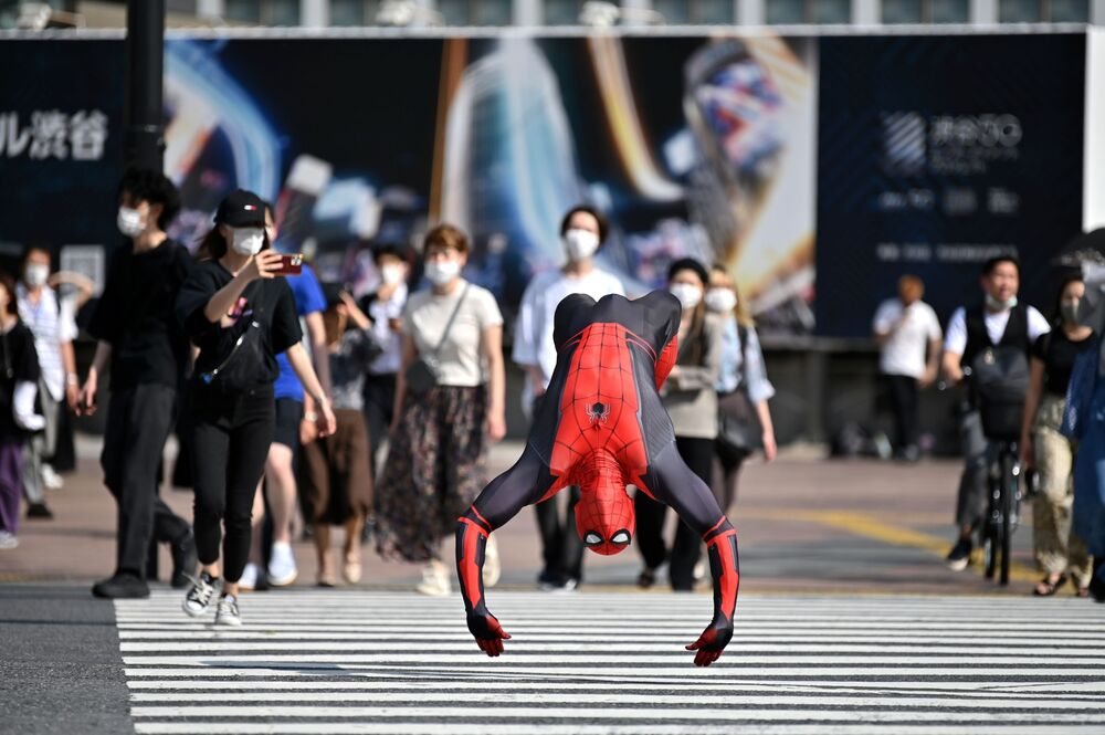 A man wearing a Spiderman costume jumps across Shibuya crossing in Tokyo on June 8, 2020.