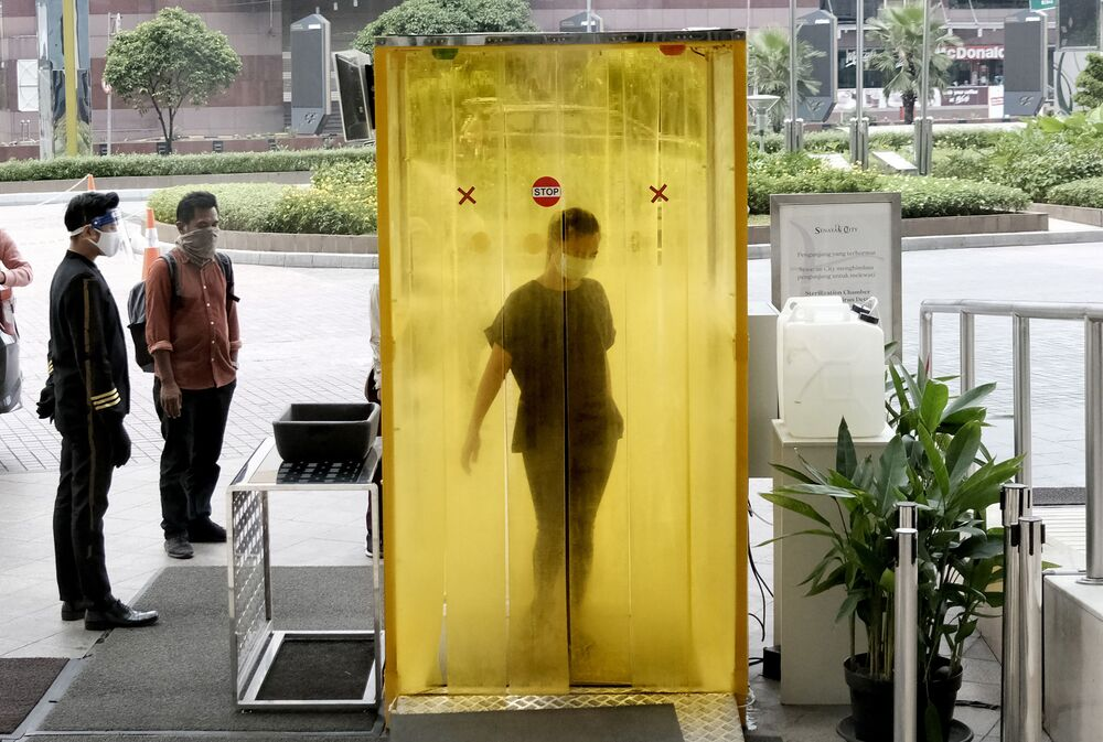 A woman reacts as she is sprayed with disinfectant inside a chamber as a precaution against the new coronavirus before entering a shopping mall in Jakarta, Indonesia, Tuesday, June 9, 2020. As Indonesia's overall virus caseload continues to rise, the capital city has moved to restore normalcy by lifting some restrictions this week, saying that the spread of the virus in the city of 11 million has slowed after peaking in mid-April.