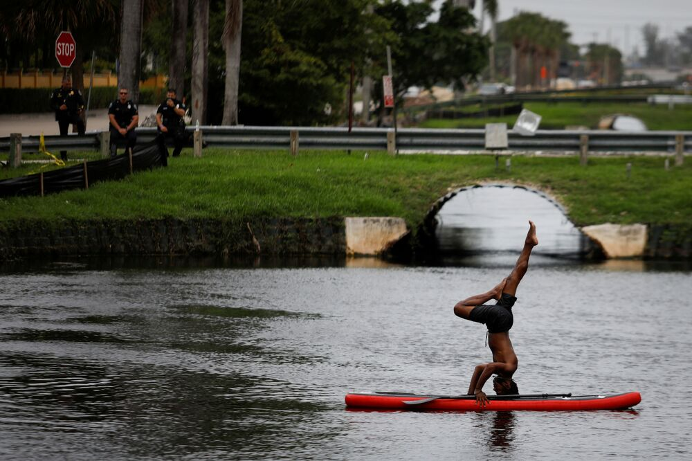 A man stands on his head on a paddle board as pollice officers look at him during a protest against racial inequality in the aftermath of the death in Minneapolis police custody of George Floyd, outside Trump National Doral golf resort in Doral, Florida, U.S., June 6, 2020.