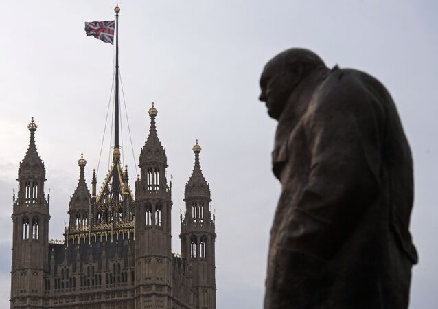 A statue of former British Prime Minister Winston Churchill stands near the Victoria Tower of the Houses of Parliament, as a British Union flag flies from a pole atop the tower, in London on December 8, 2016.