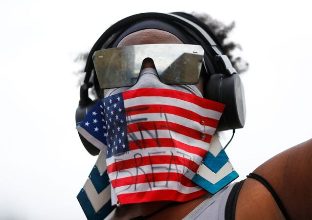CeWanda Sconiers wears an American flag with the words I can't breathe as protesters rally following the death of Manuel Ellis in Tacoma police custody in March, and the death of George Floyd in Minneapolis police custody, in Tacoma, Washington, U.S. June 5, 2020.