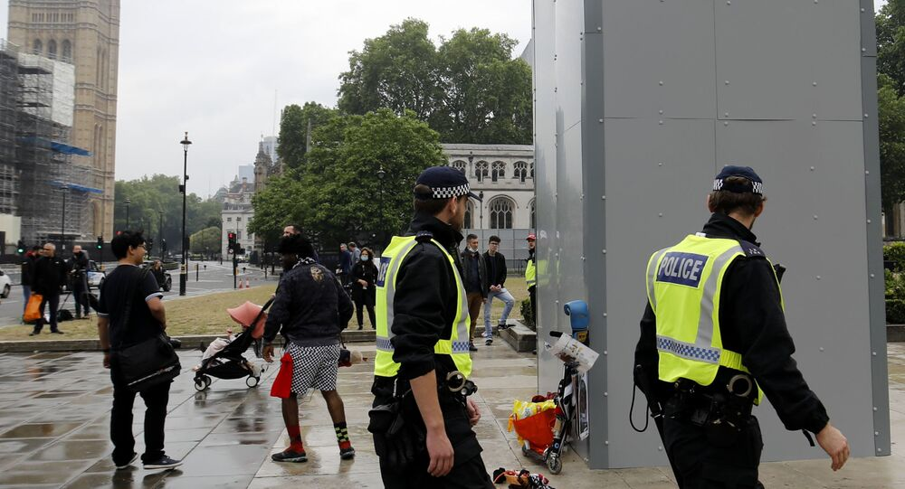 Police officers walk past a boarded-up statue of British wartime Prime Minister Winston Churchill on Parliament square in central London on June 12, 2020.