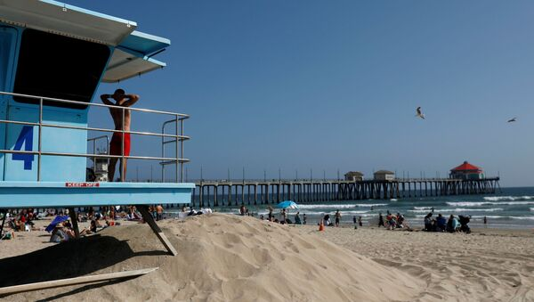 A lifeguard stretches while watching the water from a tower at the beach on Memorial Day weekend during the outbreak of the coronavirus disease (COVID-19) in Huntington Beach, California, U.S., May 23, 2020. REUTERS/Patrick T. Fallon - Sputnik International