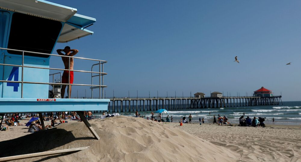 A lifeguard stretches while watching the water from a tower at the beach on Memorial Day weekend during the outbreak of the coronavirus disease (COVID-19) in Huntington Beach, California, U.S., May 23, 2020. REUTERS/Patrick T. Fallon