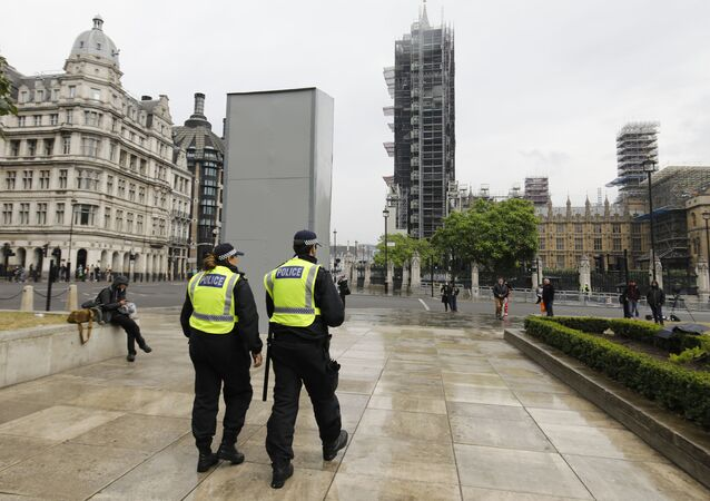 Police officers walk past a boarded-up statue of British wartime Prime Minister Winston Churchill on Parliament square in central London on June 12, 2020