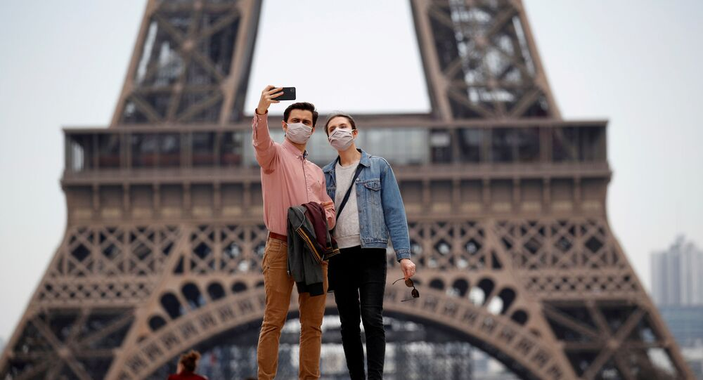 People wearing face masks take a selfie at Trocadero square near the Eiffel Tower, as France began a gradual end to a nationwide lockdown due to the coronavirus disease (COVID-19) in Paris, France, May 16, 2020