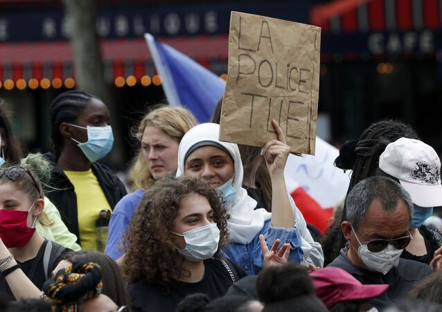 A placard read The Police Kills as people gather for a march against police brutality and racism in Paris, France