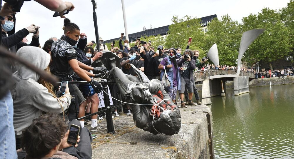 Protesters throw a statue of slave trader Edward Colston into Bristol harbour during a Black Lives Matter protest on 7 June 2020.