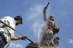 A municipal worker used a high pressure water cleaner to remove the paint from the statue of Piet Hein in Rotterdam, Netherlands, Friday, June 12, 2020. Dutch activists have spray painted the words killer and thief and daubed red paint on a statue of a man regarded by many as a naval hero from the 17th-century Golden Era of Dutch trade and colonial expansion. (AP Photo/Peter Dejong)