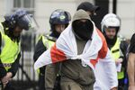 A masked protester walks as British police officers in riot gear escort him and others away in central London, as groups gather to counter-protest against a Black Lives Matter demonstration, Saturday, June 13, 2020.