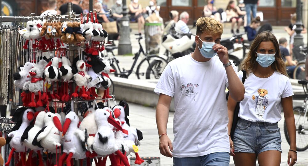 People wearing face masks pass by a gift shop on 22 May 2020 in Strasbourg