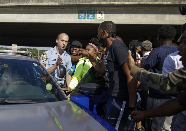 Protesters block a Georgia State Patrol official from leaving, Saturday, June 13, 2020, near the Wendy's restaurant where Rayshard Brooks was shot and killed by police Friday evening following a struggle in the restaurant's drive-thru line in Atlanta.