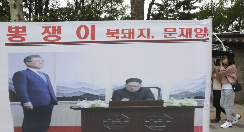 A banner showing a photo of North Korean leader Kim Jong Un and South Korean President Moon Jae-in, left, is displayed to denounce policies of Moon on North Korea in Seoul, South Korea, Saturday, June 6, 2020.