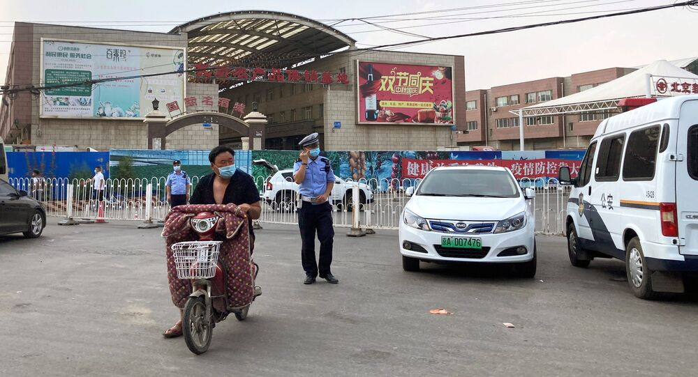 Police officers wearing face masks are seen outside the Xinfadi wholesale market, which has been closed for business after new coronavirus infections were detected, in Beijing, China June 13, 2020.