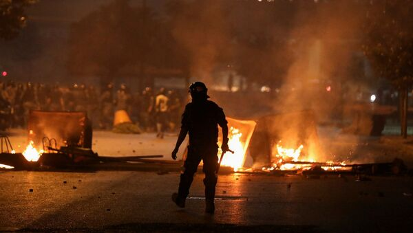 A member of the Lebanese riot police walks near a burning fire during a protest against the fall in pound currency and mounting economic hardship, in Beirut, Lebanon June 12, 2020.  - Sputnik International