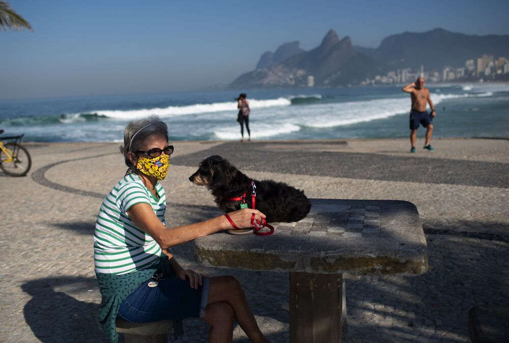 Lucia and her dog Jujuba sit at Arpoador beach, amid the coronavirus pandemic in Rio de Janeiro, Brazil, Tuesday, 2 June 2020.