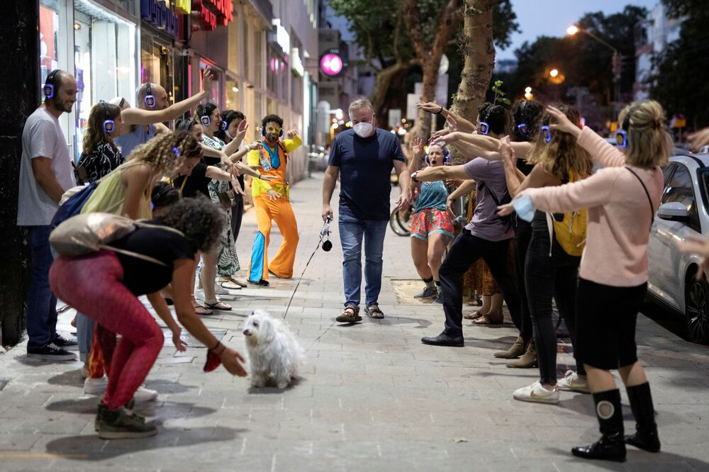 A man wears a mask and walks his dog past people taking part in a silent disco event as some businesses reopened at the end of last month under a host of new rules, following weeks of shutdown amid the coronavirus disease (COVID-19) crisis, in Tel Aviv, Israel 4 June 2020.