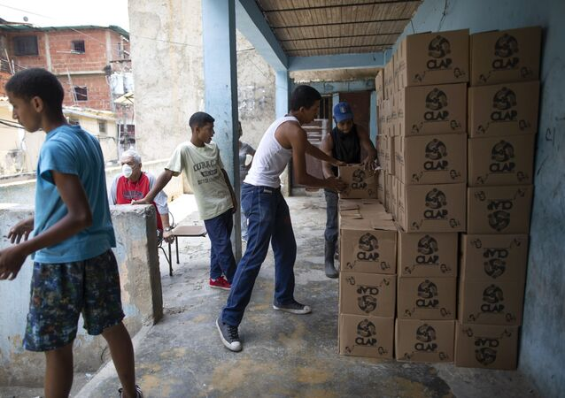 Residents help to unload and stack boxes of basic food staples, such as pasta, sugar and flour, provided by a government food assistance program, in Caracas' slum of Petare, Venezuela, Thursday, April 30, 2020.