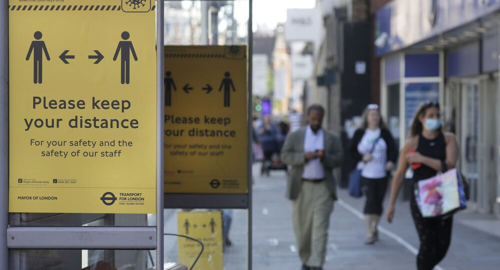 Signs advise people to social distance on a bus stop along a high street, in London, 19 May 2020, after the introduction of measures to bring the country out of lockdown amid the coronavirus pandemic.