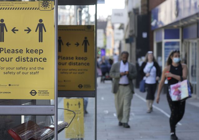 Signs advise people to social distance on a bus stop along a high street, in London, Tuesday, May 19, 2020, after the introduction of measures to bring the country out of lockdown amid the coronavirus pandemic.
