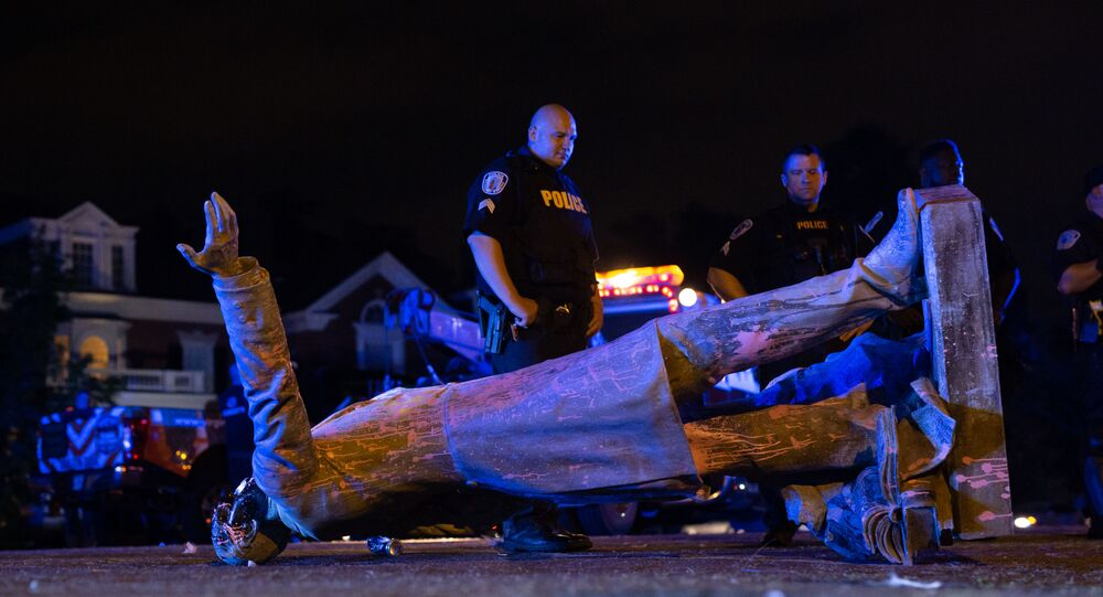 In this file photo taken on June 10, 2020 A statue of Confederate States President Jefferson Davis lies on the street after protesters pulled it down in Richmond, Virginia. - Confederate monuments are coming down and statues of Christopher Columbus are being toppled as Americans grapple with the ghosts of the country's racial history in the wake of George Floyd's death.